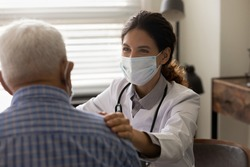 Close up smiling female doctor wearing protective face mask touching senior patient shoulder, physician comforting and supporting mature man at medical appointment, psychological help concept