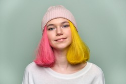 Close-up smiling female positive face, portrait of trendy teenager girl with colored dyed hair, young hipster in knitted hat on green pastel background. Adolescence, fashion, hair, beauty, lifestyle