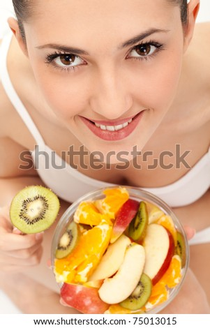 close up, smiling girl eating fresh fruit salad, on white background,  top view