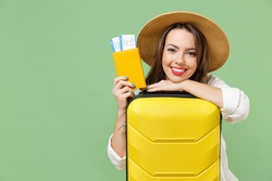 Close up smiling happy tourist woman in casual clothes hat hold passport tickets yellow suitcase valise isolated on green background Passenger travel abroad weekend getaway Air flight journey concept.