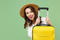 Close up smiling happy traveler tourist woman in casual clothes hat hiding with yellow suitcase valise isolated on green background Passenger travel abroad weekends getaway Air flight journey concept.