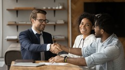 Close up smiling manager and African American family shaking hands, making successful investment or insurance deal, overjoyed young couple and realtor broker handshaking, taking loan or mortgage