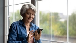 Close up smiling mature woman using smartphone, browsing apps, standing near window at home, senior grey haired female looking at phone screen, chatting or shopping online, enjoying leisure time