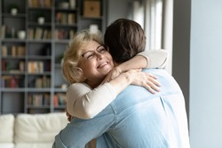Close up smiling mature woman wearing glasses hugging adult son, standing in living room at home, family enjoying tender moment, beautiful happy middle aged woman embracing young man