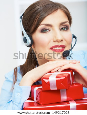 Close Up Smiling operator seat at table with red gift box. Happy business woman at office. Female business model posing.