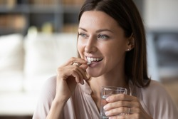 Close up smiling woman taking white round pill, holding water glass in hand, happy young female taking supplement, daily vitamins for hair and skin, natural beauty, healthy lifestyle