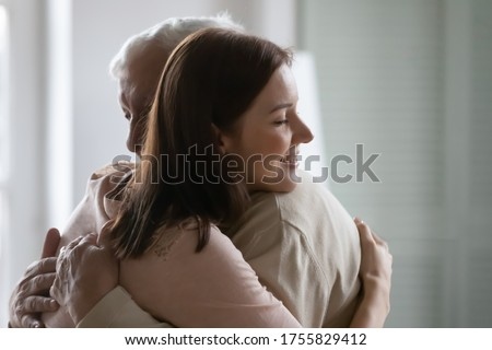 Close up smiling young beautiful woman hugging older man, happy grownup daughter and mature father enjoying tender moment with closed eyes, cuddling, two generations, good family relationship