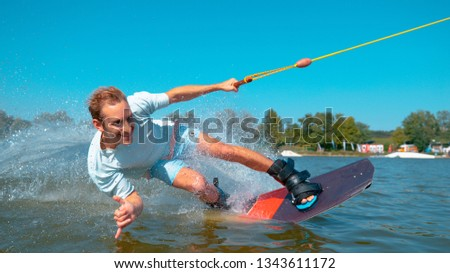 CLOSE UP: Smiling young blonde haired wakeboarder dude gives the shaka sign as he surfs past camera. Cinematic shot of an athletic Caucasian man wakesurfing on the lake and giving the surf's up.