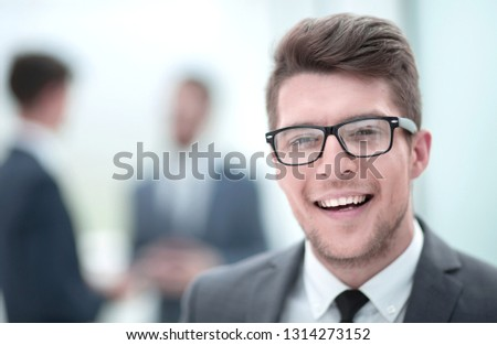 close up.smiling young businessman in the office background #1314273152