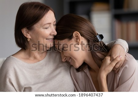 Close up smiling young woman and mature mother hugging, elderly mum and grownup daughter enjoying tender moment, cuddling, holding hands, happy family spending leisure time at home together