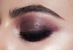 Close-up smokey eyes make-up. purple make-up with golden shimmer