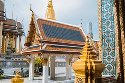 Close-up snapshot of richly decorated buildings in Wat Phra Kaew, Emerald Buddha Temple, Bangkok, Thailand. Discovering of east-Asia culture by visiting of tourist attraction. Historic heritage.