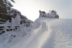 close-up: snow clouds in the form of a sea wave against the background of bizarre rocks. frozen snow avalanche like ice cream. winter mountain valley with a white texture of snow after a big snowfall