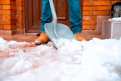 Close up Snow shoveling in front of the brick House on winter day