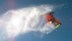 CLOSE UP: Snowboarder jumping big air kicker, spraying snowflakes and flying over sun on perfect winter day. Snowboard jump in snow park. Sunbeams shining past jumping boarder in mountains