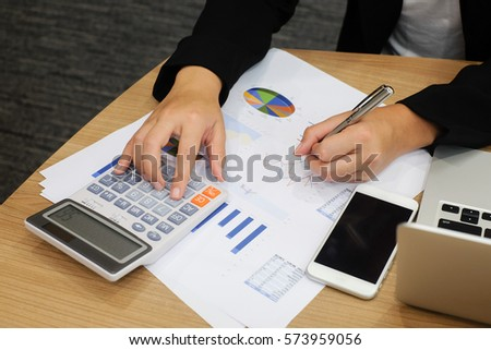 close up soft focus of woman hand writing on paperwork and press button calculator