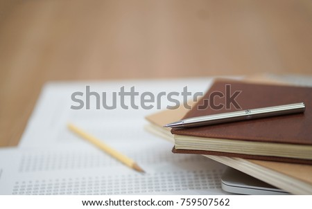 close up soft focus on Clutch-type pencil lay on notebook and exam sheet test paper:blur picture concept.