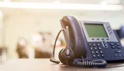 close up soft focus on telephone devices at office desk for customer service support (call center) concept
