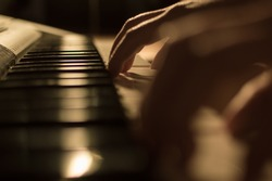 Close-up soft focused atmospheric photography of a hand playing the piano keys. Concept: Music creating, composing, lyrics, performance