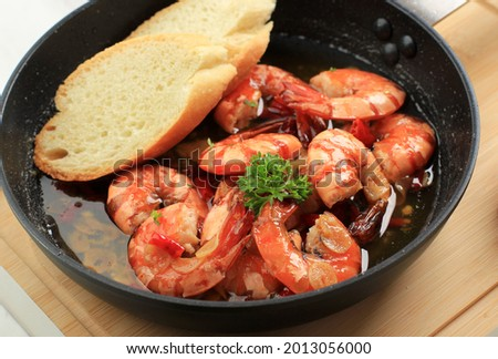 Close Up Spanish Gambas with Oil (Ajillo). Shrimp Scampi. Traditional Spanish Tapa with Prawns Cooked in Oil with Garlic and Chilli. Served with Slice Baguette Foto d'archivio ©