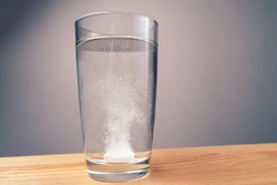 Close up sparkling water glass with dissolving effervescent aspirin pill standing on wooden table