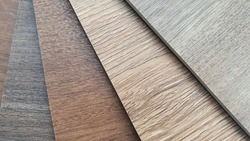 close up spc (stone composite) vinyl tile samples swatch containing multi color of chestnut and oak wooden texture surface. macro interior wooden flooring material.