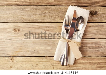 Close up Spoon, Fork and Knife Tied on White Napkin with Empty Tag, on Wooden Table with Text Space.