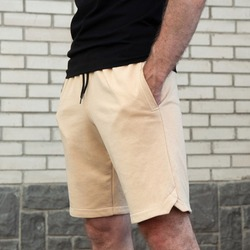 close-up sports men's sand-colored shorts on a man against a white brick wall, square photo