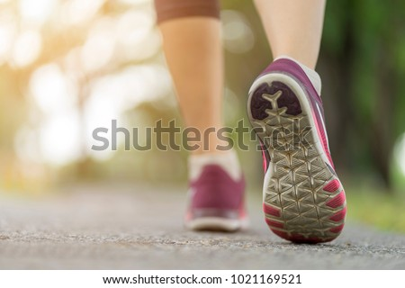 Close up, Sporty women shoe running on the road, feet to walking or jogging alone at park, Sports healthy lifestyle concept.