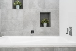 Close-up - square on - photo of bathtub with grey tiling with floor to ceiling, modern faucet/tap, and small artificial plants.