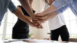 Close up stack hands over table of diverse international company workers. Mixed race young colleagues joining hands, showing support before starting new project, involved in teambuilding activity.