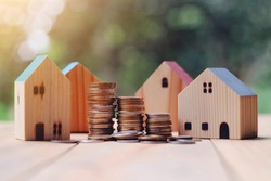 close up stack of coin and toy wooden house on wood table, saving and manage money to success home business, property insurance, subprime mortgage crisis risk and problem concept