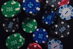 Close up stack of different colored poker chips of diverse value isolated on the black casino table background. Gambling tournament betting for success.