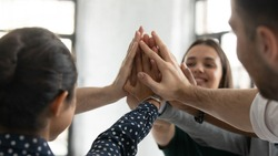 Close up stacked palms of diverse business people gathered together in office celebrating successful project accomplishment, giving high five as symbol of trust, unity, support, team building concept