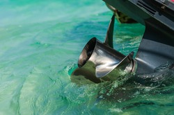 Close up stainless steel motor boat propeller on turquoise sea water background.