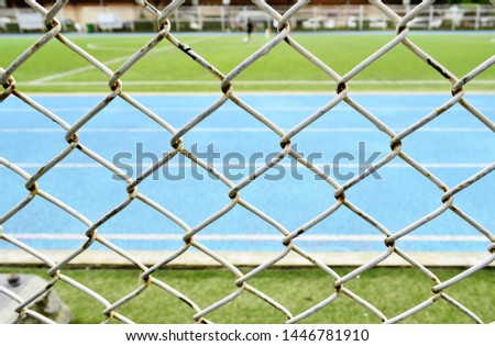 Close up Steel fence.The football field and the blue light running track behind the steel fence of the stadium.