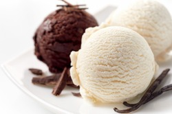 Close Up Still Life of Scoops of Vanilla and Chocolate Ice Cream with Chocolate Shavings and Vanilla Beans on White Platter in front of White Background