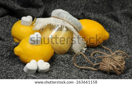 close up still life with a creamy lemon curd jar and bright yellow lemons decorated with chalk hearts and linen on grey background