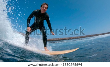 CLOSE UP: Stoked surfboarder smiling as he rides a wave to the sunny coast in Spain. Young Caucasian man in black wetsuit cheerfully enjoying a sunny day surfing in clear ocean water of Fuerteventura. #1350295694