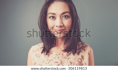 Close up straight face. Vintage, retro style of portrait of Asian woman in pink vintage dress on blue - green background.