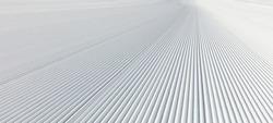 Close-up straight line rows of freshly prepared groomed ski slope piste.