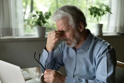 Close up stressed mature man massaging nose bridge, holding glasses, sitting at desk with laptop, elderly grey haired male suffering from eye strain, dry eyes syndrome after long laptop use