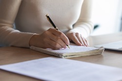 Close up student girl sit at desk holding pen makes notes on exercise book, do task prepare for college exams, female entrepreneur write down important data information creative start up ideas concept