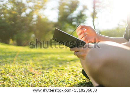 close up student hand holding and write notebook in green garden and Copyspace #1318236833