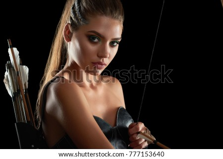Close up studio portrait of a beautiful young female archer looking to the camera posing on black background seductively sexy sexuality femininity beauty archery fighter warrior weapon cosplay.