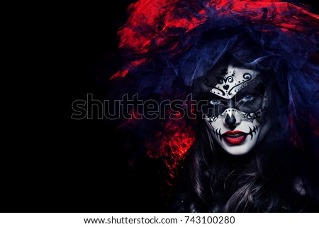 Close up studio portrait of beautiful woman with Halloween sugar skull makeup in red and black colors, wearing bridal veil. Model looking at camera. Dark, dead bride. Copy, empty space for text.    Foto d'archivio ©