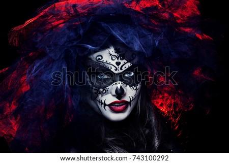 Close up studio portrait of beautiful woman with Halloween sugar skull makeup in red and black colors, wearing bridal veil. Model looking at camera. Dark, dead bride.  Foto d'archivio ©