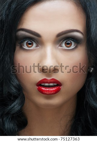 Close-up studio portrait of beautiful young woman with bright makeup and hairstyle looking surprised