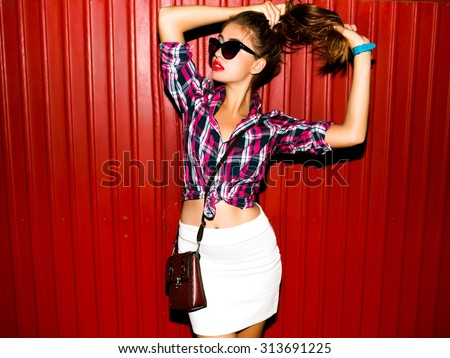 Stock Photo Close up studio portrait of cheerful blonde hipster girl going crazy making funny face and showing her tongue.high fashion portrait of young elegant woman takes her ponytail,black glasses,red lips
