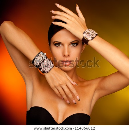 close-up studio portrait of young beautiful tanned woman with long acrylic leopard nails and makeup